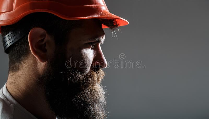 Gebaarde mensenarbeider met baard in de bouw van helm of bouwvakker Mensenbouwers, de industrie De burgerlijke bouwer van de port royalty-vrije stock foto's