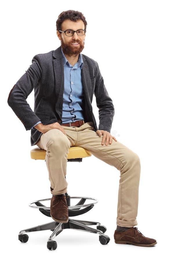 Gebaarde mensenzitting op een stoel stock foto