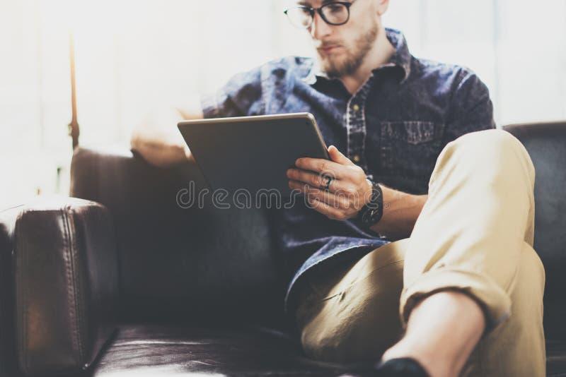 Gebaarde op de markt brengende specialist die digitaal de Zolderbureau werken van het tablet modern Binnenlands Ontwerp De mens o stock foto