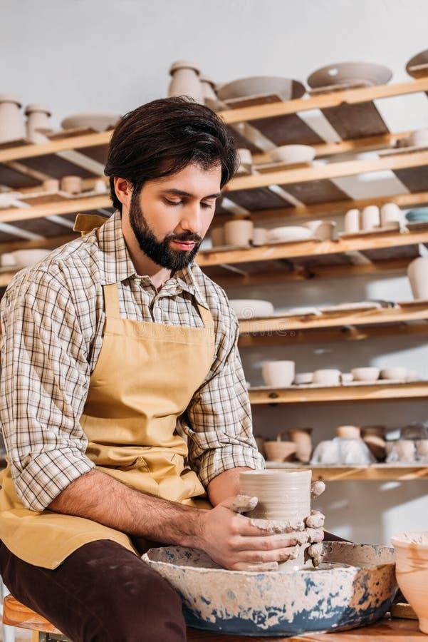 gebaarde pottenbakker die ceramische dishware op aardewerkwiel maken royalty-vrije stock foto's