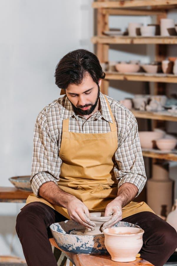 gebaarde pottenbakker die ceramische pot op aardewerkwiel maken stock afbeeldingen