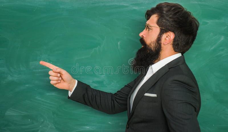 Gebaarde professor bij schoolles bij bureaus in klaslokaal Onderwijs de ruimte van het bordexemplaar Vriendschappelijke leraar bi royalty-vrije stock foto