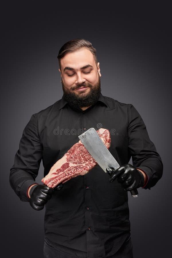 Gebaarde slager met vlees en mes royalty-vrije stock fotografie
