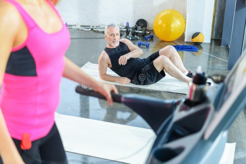 Gebaarde sportman die op mat liggen en vrouw het uitoefenen op tredmolen bekijken stock fotografie