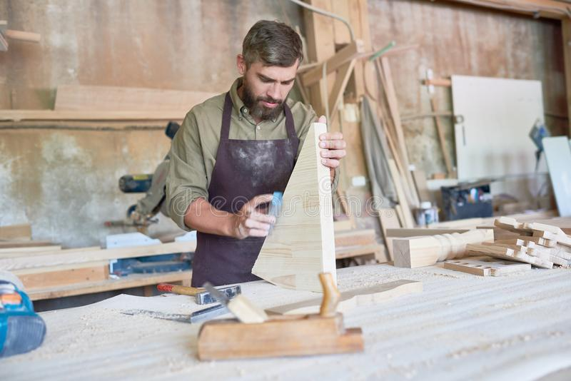 Gebaarde Timmerman Sanding Wooden Parts in Workshop royalty-vrije stock fotografie