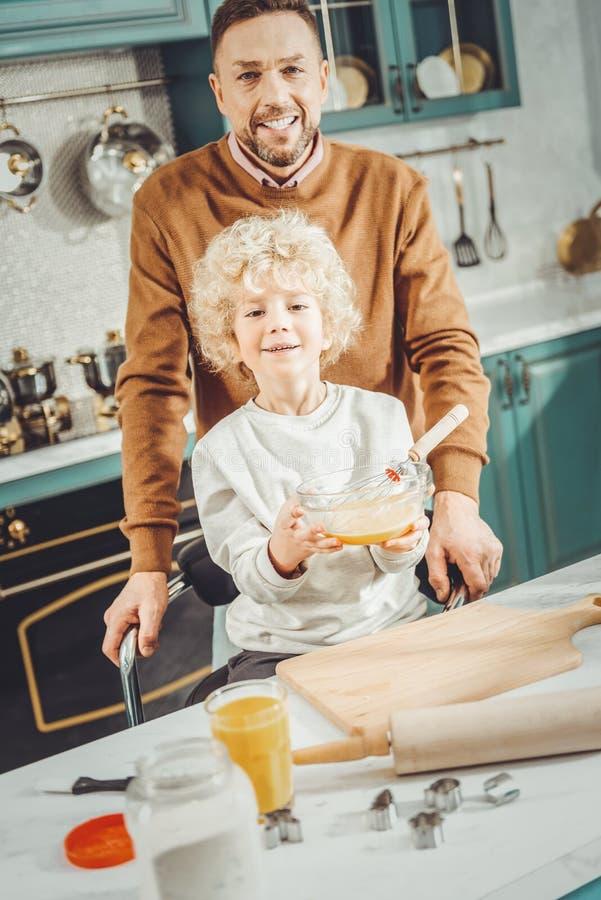 Gebaarde vader en krullende zoon die zich in moderne ruime keuken bevinden royalty-vrije stock fotografie