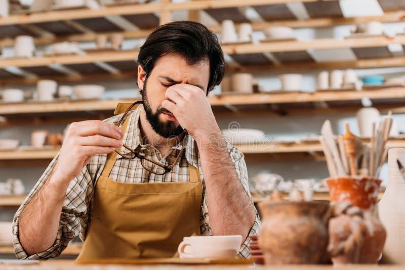 gebaarde vermoeide pottenbakker in schortzitting in workshop met ceramische dishware royalty-vrije stock foto's