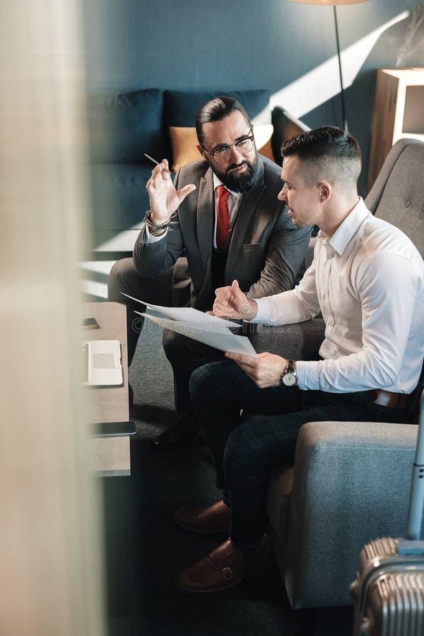 Gebaarde werkgever die glazen dragen die sommige instructies zijn werknemer geven royalty-vrije stock afbeeldingen