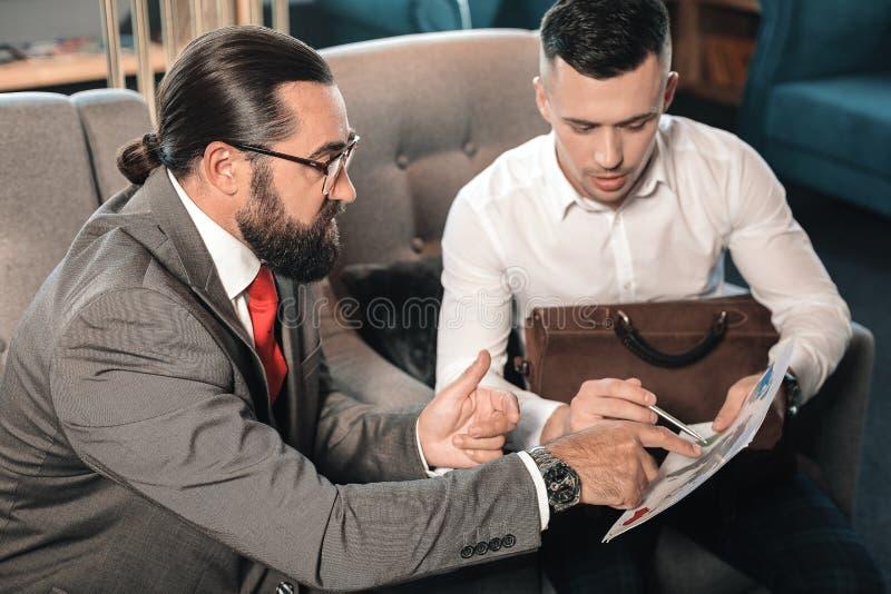 Gebaarde werkgever die het werk ogenblikken verklaren aan zijn jonge stagiair stock afbeelding