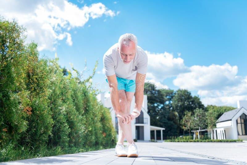 Gebaarde zakenman die blauwe borrels en witte tennisschoenen dragen die benen uitrekken royalty-vrije stock foto