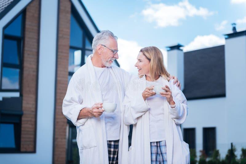 Gebaarde zakenman die glazen dragen die zijn aantrekkelijke glimlachende vrouw koesteren royalty-vrije stock fotografie