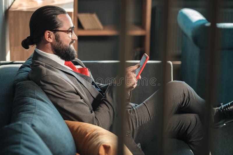 Gebaarde zakenman die grijs kostuum en rode band dragen die zijn telefoon houden stock foto's