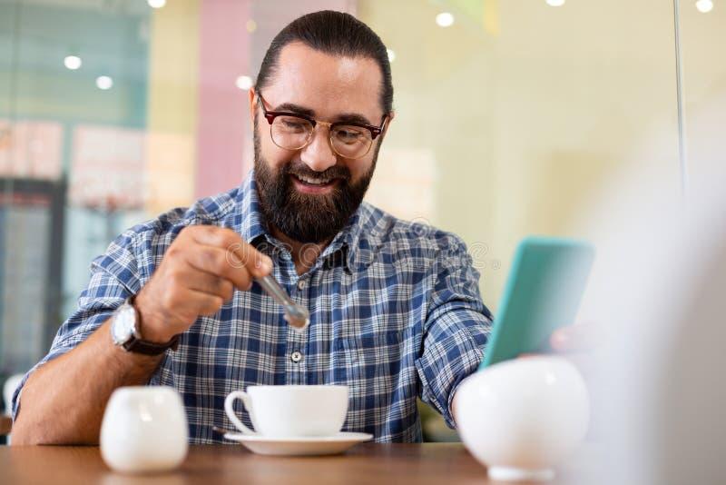 Gebaarde zakenman die leerhorloge op zijn hand dragen die koffie hebben stock afbeelding
