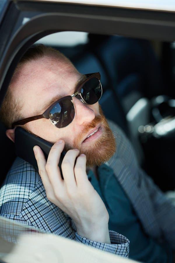 Gebaarde zakenman die op telefoon binnen van auto spreken royalty-vrije stock foto's