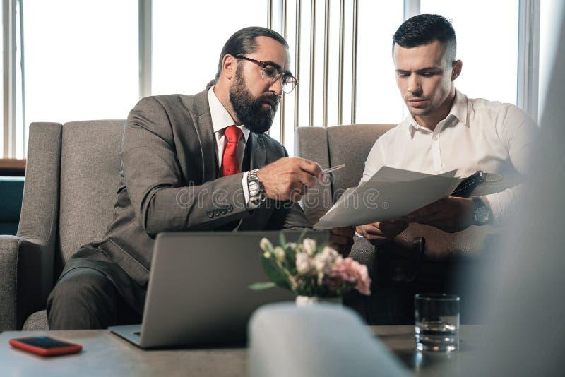 Gebaarde zakenman die pen geven aan zijn partner die contract ondertekenen stock foto's