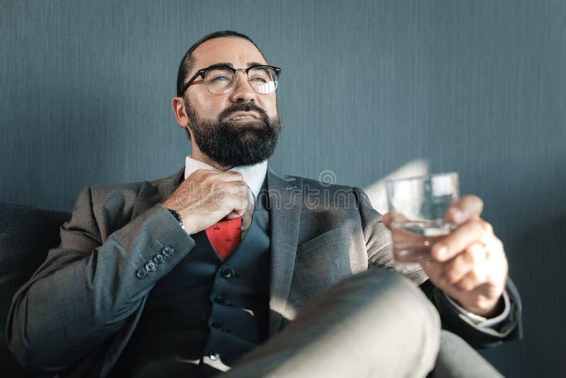 Gebaarde zakenman die wat water drinken vóór belangrijke vergadering stock afbeeldingen