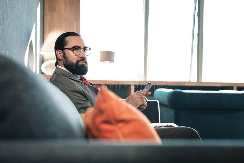 Gebaarde zakenman die zijn rode smartphone houden terwijl het hebben van onderbreking royalty-vrije stock foto's