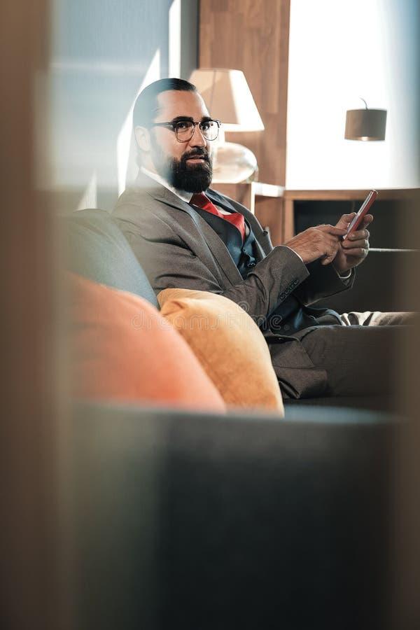 Gebaarde zakenmanzitting op grijze bank met oranje kussens royalty-vrije stock foto