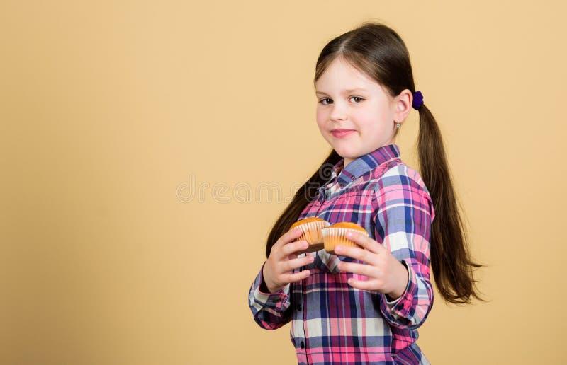 Gebacken durch mich Nettes kleines Mädchen mit frisch gebackener Nachtischnahrung Entzückendes kleines Kind, das gebackene Hauptm stockfotografie
