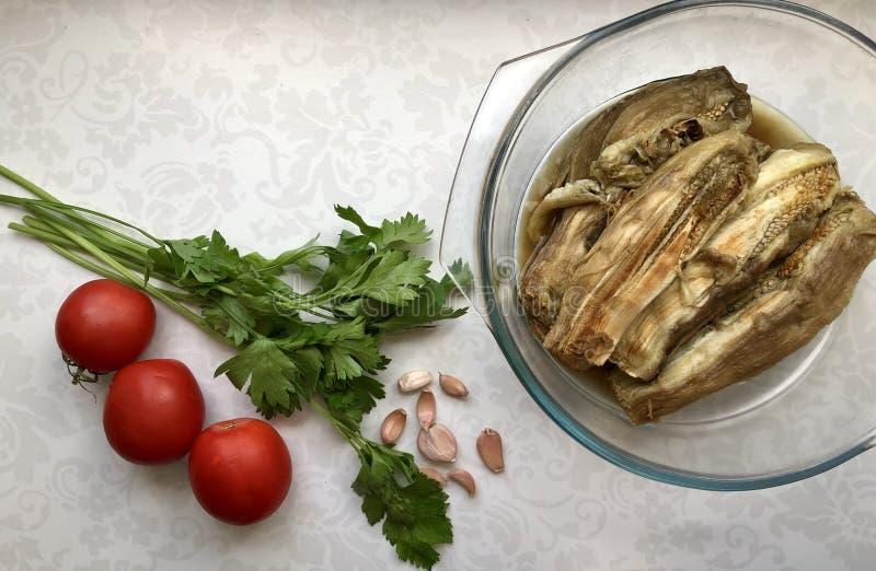 Gebackene Auberginen in einer Glasschüssel, grüne Petersilie, frische Tomaten, Knoblauch stockbild