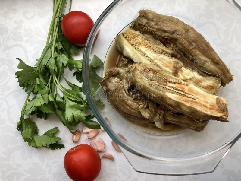 Gebackene Auberginen in einer Glasschüssel, grüne Petersilie, frische Tomaten, Knoblauch stockfotografie