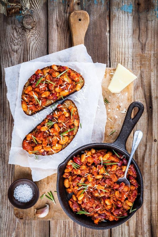Gebackene Bohnen mit Rosmarin und Parmesankäse auf Toast stockfoto