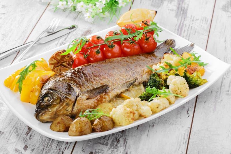 Gebackene Fische mit Gemüse stockfotos