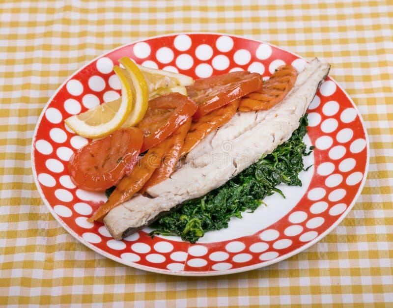 Gebackene Fischfilet mit Regenbogenforelle mit gedämpftem Gemüse und gekochtem Spinat und mit einer Scheibe der Zitrone stockfotos