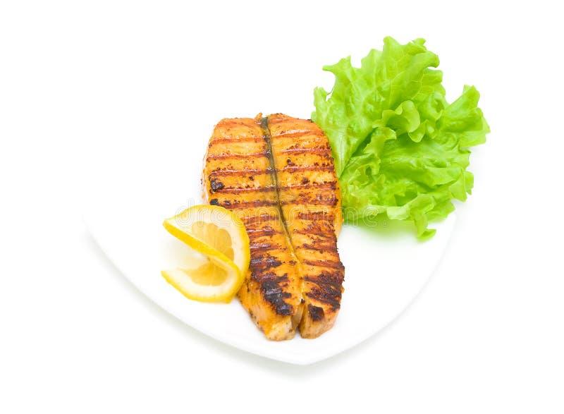 Gebackene Forelle, Zitrone und Kopfsalat auf einem weißen Hintergrund stockbild