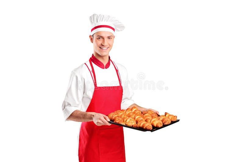 Gebackene Hörnchen einer männliche Bäckerholding frisch stockfotografie