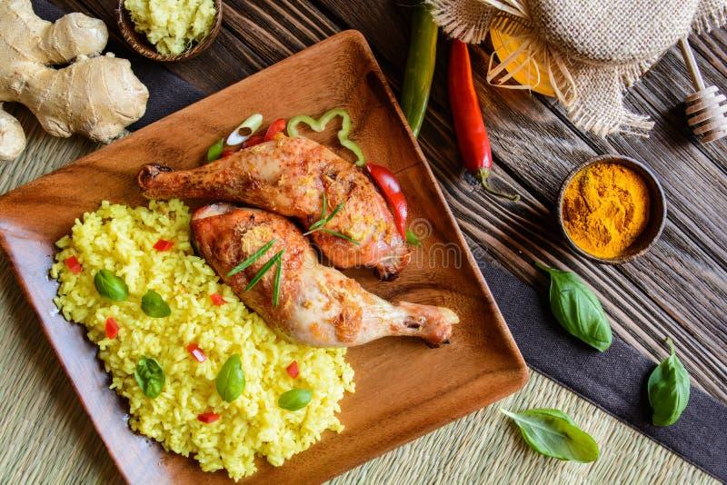Gebackene Hühnerschenkel mit Honig, zerriebenem Ingwer und Reis mit Gelbwurz lizenzfreie stockbilder