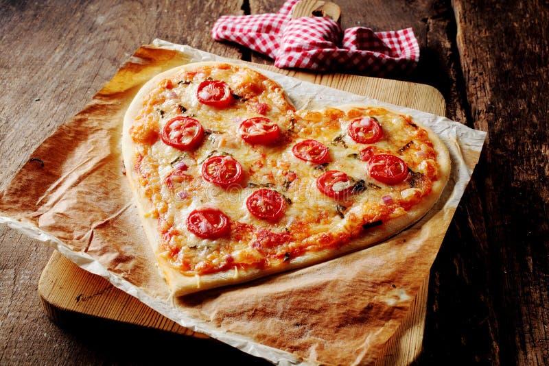 Gebackene Herz-förmige Pizza überstiegen mit Tomatenscheiben lizenzfreies stockfoto