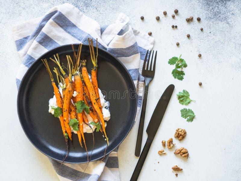 Gebackene junge orange Karotten mit Weichkäse, Walnüssen und Koriander auf Schwarzblech Beschneidungspfad eingeschlossen stockfoto