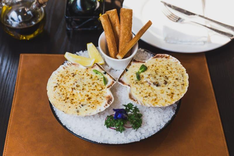 Gebackene Kamm-Muscheln mit Käse dienten mit geschnittenen Zitronen- und Brotstöcken auf Schüssel mit voll Seesalz lizenzfreie stockfotos