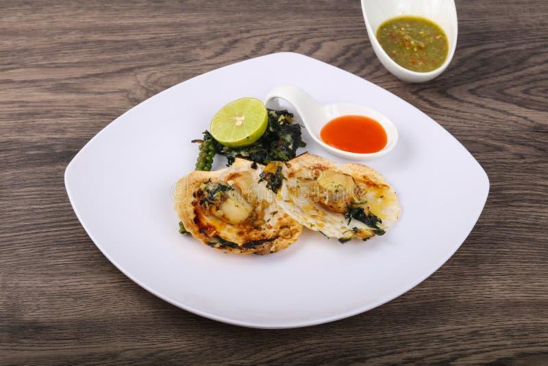 Gebackene Kamm-Muscheln mit Spinat stockfotos