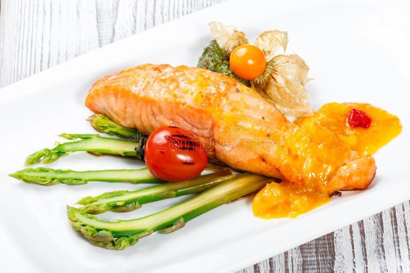 Gebackene Lachse geschmückt mit Physalis, Spargel, Tomaten mit Kräutern auf hölzernem Hintergrund Heißes Fischgericht stockfoto