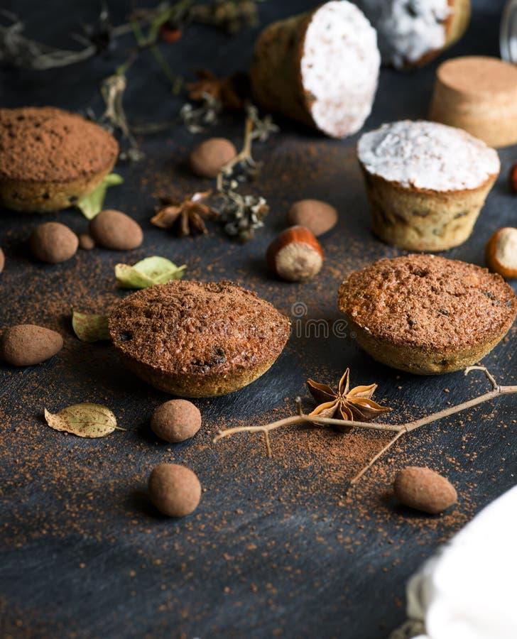 Gebackene Muffins werden mit Kakao auf einer schwarzen Oberfläche besprüht stockfoto