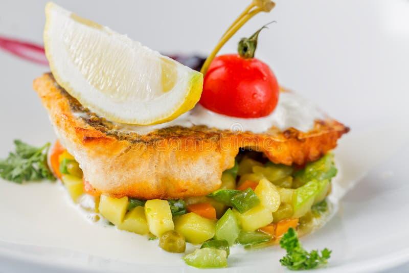 Gebackene Stangenleiste mit Tomate, Zitrone und Gemüse auf weißer Platte Schließen Sie herauf Bild mit selektivem Fokus lizenzfreies stockbild