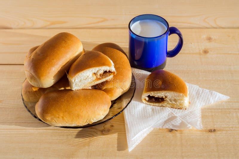 Gebackene Torten mit einer süßen Füllung liegen auf einer Platte nahe bei einem Becher Milch stockfotografie
