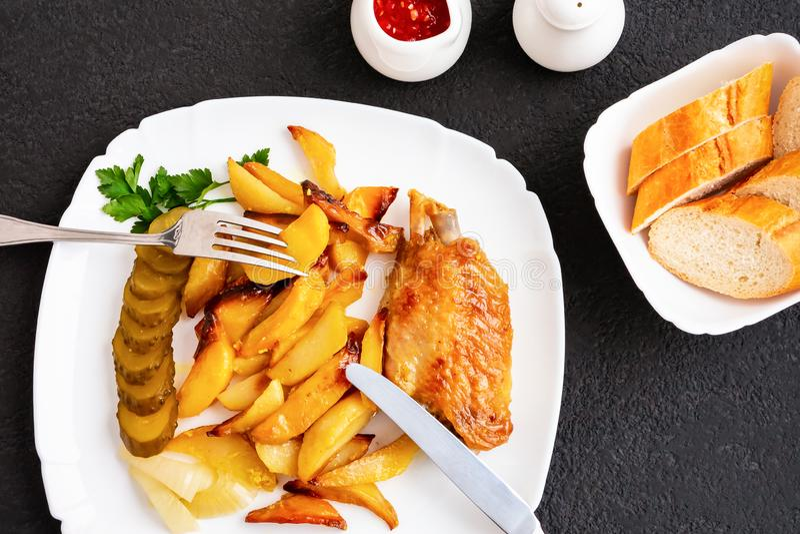 Gebackene Truthahnflügel mit Kartoffelstücken auf einer weißen Platte auf einem schwarzen Küchentisch mit Remoulade und Tomat stockfotografie