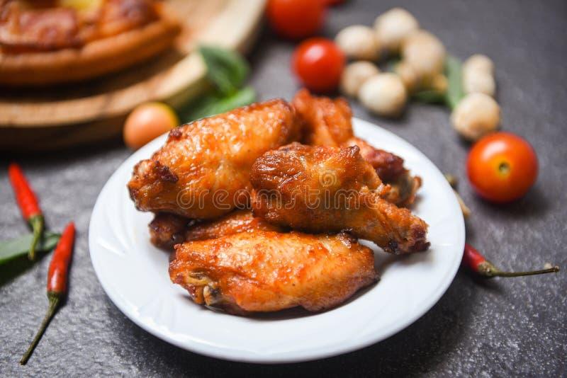 Gebackener Hühnerflügel bbq-Grill auf heißem und würzigem Huhn der Platte - und Soße auf dunklem Hintergrund stockfotografie