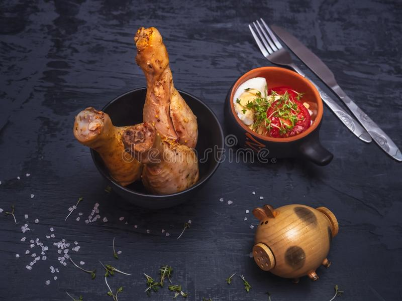 Gebackener Hühnertrommelstocksalat von Tomatenhälften und von Scheiben des gekochten Eies auf einem dunklen Hintergrund stockfoto