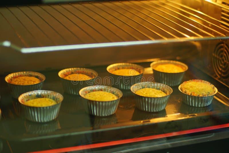Gebackener kleiner Kuchen innerhalb des elektrischen Ofens für Parteizeit lizenzfreie stockbilder