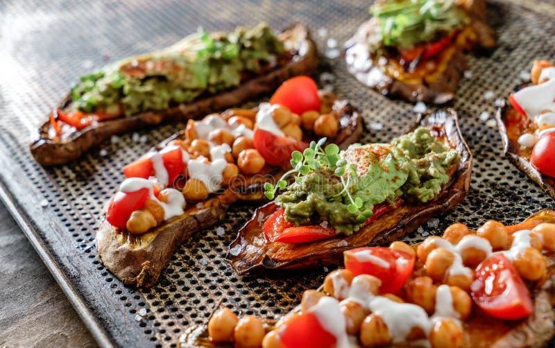 Gebackener Süßkartoffeltoast mit gebratenen Kichererbsen, Tomaten, Ziegenkäse, Soßenguacamole, Avocado, Sämlinge auf Backblech lizenzfreies stockbild