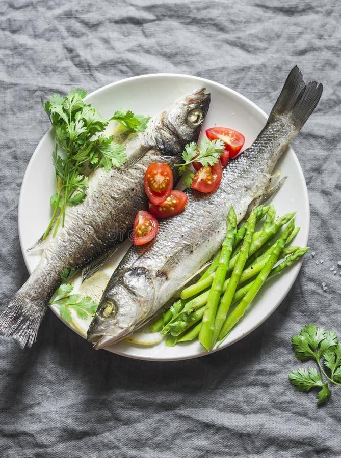 Gebackener Wolfsbarsch mit Spargel und Tomaten Lebensmittelkonzept der gesunden Diät auf einem grauen Hintergrund stockfotos