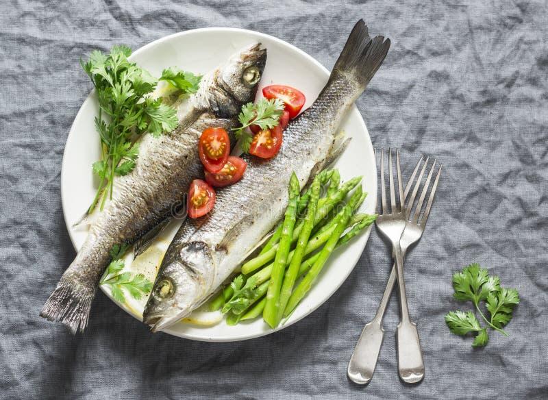 Gebackener Wolfsbarsch mit Spargel und Tomaten Lebensmittelkonzept der gesunden Diät auf einem grauen Hintergrund lizenzfreie stockbilder
