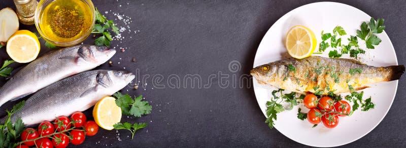 Gebackener Wolfsbarsch und frische Fische mit Bestandteilen für das Kochen lizenzfreie stockfotografie