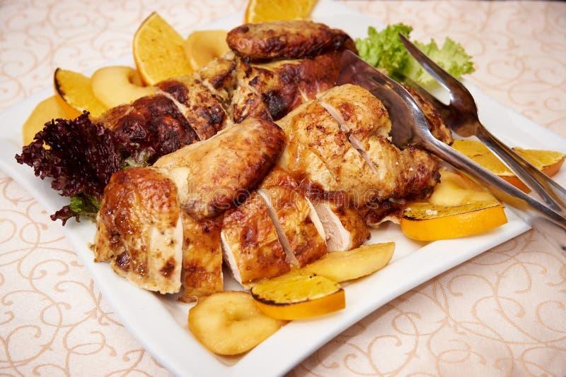 Gebackenes Fleisch mit orange Scheiben auf einer weißen Platte lizenzfreie stockfotografie