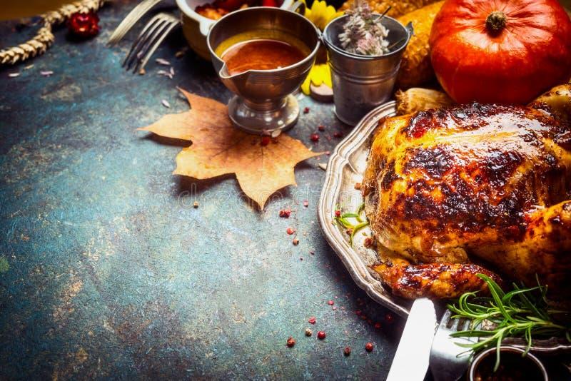 Gebackenes ganzes Huhn oder kleiner Truthahn mit Soße, Kürbis und Herbstdekoration dienten für Danksagungs-Tag stockfoto