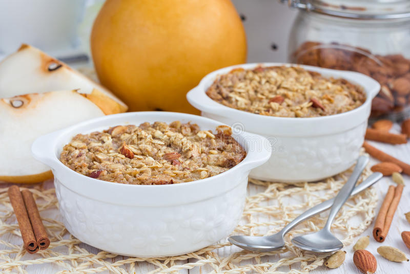 Gebackenes Hafermehl mit Nüssen, Mandelmilch, Gewürzen und asiatischer Birne lizenzfreies stockbild